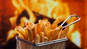 French fries served in metallic mesh recipient - on fire background royalty free stock image