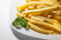 French Fries. Served on white plate, decorated with a branch of parsley Royalty Free Stock Photos