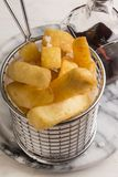 French fries in a serving basket, served with malt vinegar. In a bottle royalty free stock photo