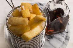 French fries in a serving basket, served with malt vinegar. In a bottle stock image
