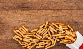 French fries spilled on the table from paper holder - copy space Royalty Free Stock Images
