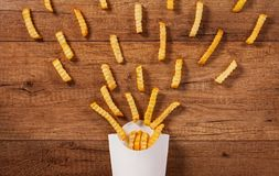 French fries spreading out of a paper holder bag Stock Photos