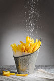 French fries sprinkled with salt in an iron bucket royalty free stock photos