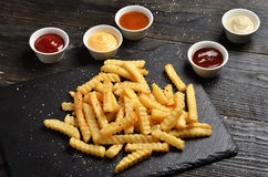 French fries on stone plate with sauces Royalty Free Stock Photos