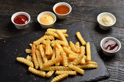 French fries on stone plate with sauces Royalty Free Stock Photo
