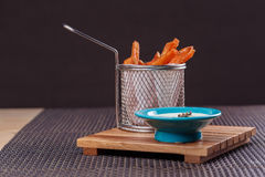 French fries sweet potatoes served in frying basket with sauce, on wooden board over brown texture background. Stock Photography