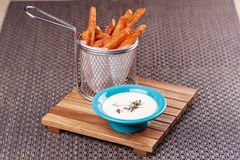 French fries sweet potatoes served in frying basket with sauce, on wooden board over brown texture background. Stock Image