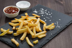French fries and tomato sauce on a blackboard Stock Image