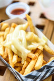 French Fries on Toping Cheese in Paper Box. Royalty Free Stock Image