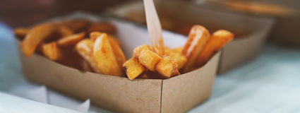 French fries on tracing paper on board on wooden table Royalty Free Stock Photography