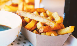 French fries on tracing paper on board on wooden table Royalty Free Stock Image