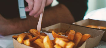 French fries on tracing paper on board on wooden table Royalty Free Stock Photo
