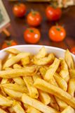 French fries in white bowl and tomato on wooden table.  royalty free stock photos