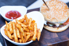French fries on white plate with ketchup and burger. Focus on fries Stock Photos