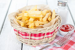 French fries in a wicker basket on white table - bar or fast food menu. French fries in a wicker basket on white wood table with salt shaker and ketchup - rural Stock Image