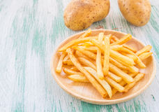 French fries on a wooden background Royalty Free Stock Images