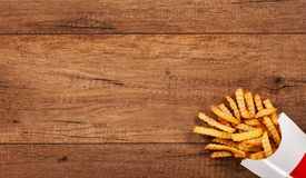 French fries on wooden table - large copy space Stock Photos