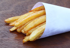 French fry. Closeup of french fry on wooden surface Royalty Free Stock Photo