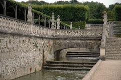 French garden detail. Part of a french renaissance garden with stairs, water, bridges and hedges Stock Photos