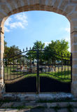 French garden with wrought iron gate. A garden in southern France viewed through an archway with black wrought iron gate stock image