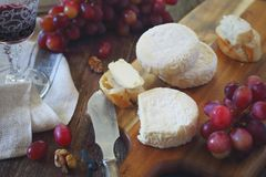 French Goat cheese, red grapes and glass of red wine. On wooden cutting board. Toned image, focus selective Stock Image