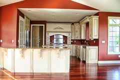 French gourmet kitchen. A view of a beautifully decorated French gourmet kitchen with white cupboards, red walls and shiny Brazilian hardwood floor Stock Photo