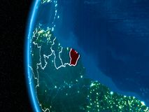 French Guiana on Earth at night. Space orbit view of French Guiana highlighted in red on planet Earth at night with visible country borders and city lights. 3D Royalty Free Stock Photo