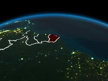 French Guiana on Earth at night. Space orbit view of French Guiana highlighted in red on planet Earth at night with visible country borders and city lights. 3D Stock Photo