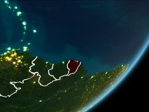 French Guiana on night Earth. French Guiana as seen from Earth's orbit on planet Earth at night highlighted in red with visible borders and city lights. 3D Royalty Free Stock Photography