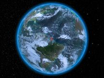 French Guiana at night on Earth. Night view of French Guiana highlighted in red on planet Earth with atmosphere and clouds. 3D illustration. Elements of this Stock Image