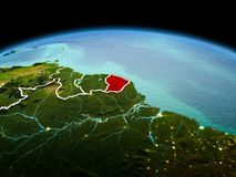 French Guiana on planet Earth in space. Morning above French Guiana highlighted in red on model of planet Earth in space with visible border lines and city Stock Image