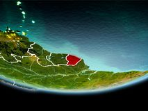 French Guiana in red in the evening. Country of French Guiana in red on planet Earth in the evening with visible border lines and city lights. 3D illustration Royalty Free Stock Image