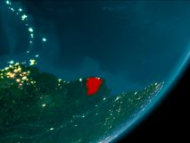 French Guiana from space at night. Night view of French Guiana highlighted in red on planet Earth with atmosphere. 3D illustration. Elements of this image Stock Photography