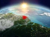 French Guiana from space in sunrise. Satellite view of French Guiana highlighted in red on planet Earth with clouds during sunrise. 3D illustration. Elements of Royalty Free Stock Photos