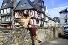 French girl with baguettes. French happy smiling girl with baguettes on the background of  old colombage houses. Morlaix, France royalty free stock photography