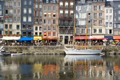 French harbor in Normandy. Quaint French harbor with restaurants and tourists Royalty Free Stock Images