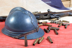 French helmet of the First World War with a gun on a blue white Royalty Free Stock Image