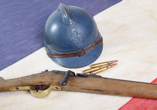 French helmet of the First World War with a gun on a blue white Stock Photos