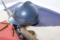French helmet of the First World War with a gun on french flag. French military helmet of the First World War with a gun on a blue white red flag Stock Photos