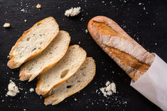 French homemade baguette bread. Wheat baguette on black shale. Cut baguette, top view stock photo