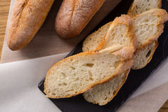 French homemade baguette bread. Wheat baguette on black shale. Cut baguette on the wooden table royalty free stock image