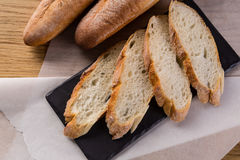 French homemade baguette bread. Wheat baguette on black shale. Cut baguette on the wooden table royalty free stock photo