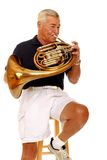 French Horn. A senior musician playing his French Horn.  Isolated on white Royalty Free Stock Photography
