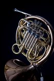 French Horn On black. A gold brass French  Horn isolated on a black background in the vertical format with  copy space Stock Photo