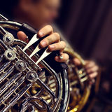 French horn in the hands of a musician. Hands of the man playing the French horn closeup Stock Image