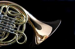 French Horn Isolated on Back. A brass and copper French horn isolated against a black background in the horizontal format with copy space Royalty Free Stock Photo