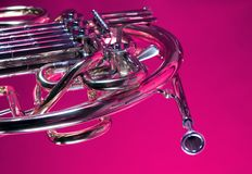French Horn Isolated On Pink. A gold French Horn isolated against a pink background in the horizontal format Royalty Free Stock Image