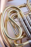 French Horn Isolated on White. A French Horn tuning slide section close up against a high key white background in the vertical format Royalty Free Stock Photography