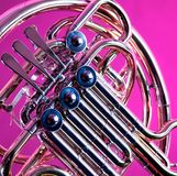 French Horn on Pink Background. A gold French Horn isolated against a pink background in the square format Stock Image