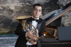 French horn player. Hornist playing brass orchestra music instrument. Portrait against the backdrop of the sea landscape. French horn player. Hornist playing stock image